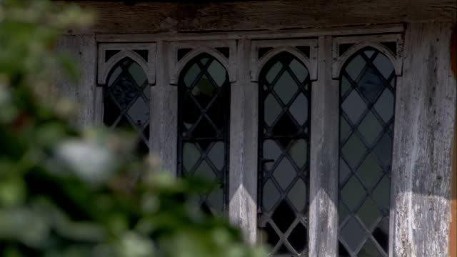 glass panes cover a window on a medieval house in lavenham, england. available in hd. - lavenham stock-videos und b-roll-filmmaterial