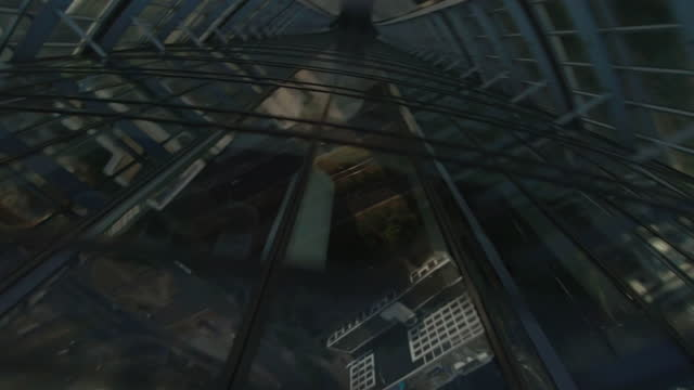 glass skyscraper reflecting the blue sky. fpv drone moving upside down the building after quick turn - office block exterior stock videos & royalty-free footage