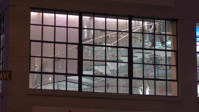 a glass window in the evening.  there is a glass staircase behind the window that people are going up and down.  the apple store - apple store stock videos & royalty-free footage