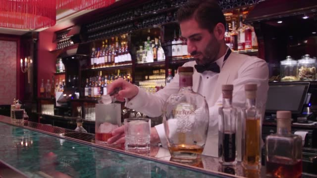 glass with a cube of ice sits on the bar at the park chinois restaurant in mayfair london united kingdom on friday jan 22 bar man pours a measure of... - garnish stock videos and b-roll footage
