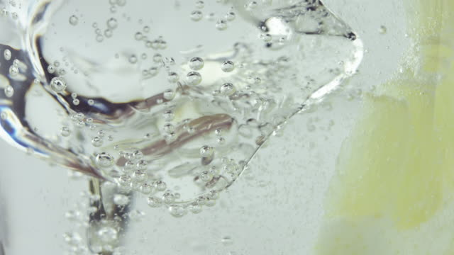 glass with cold carbonated drink and a slice of lemon falling - mixing stock videos and b-roll footage