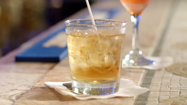 r/f td glass with whiskey cocktail placed on sinatra napkin on bar counter - male likeness stock videos & royalty-free footage