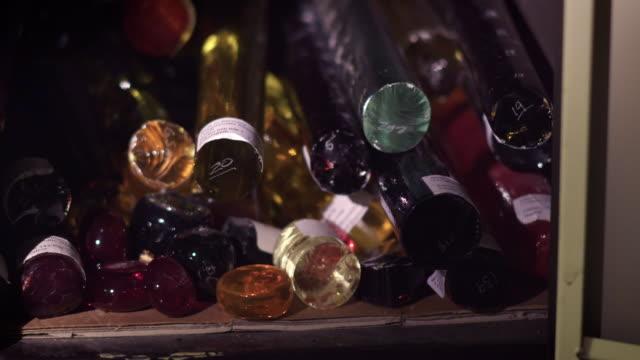 vídeos y material grabado en eventos de stock de a glassblower searches through sticks of cold glass. - forma de barra