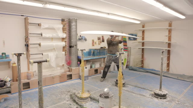 ws glasser putting long board on glassing table / wadebridge, cornwall, united kingdom - 作業場点の映像素材/bロール