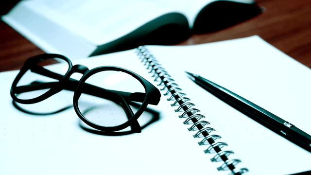 Glasses And Open Empty Notebook On Office Desk Close Up