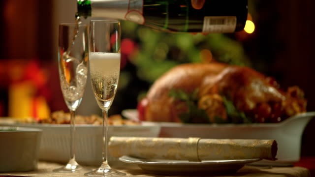 slo mo glasses being poured with champagne at christmas table - table stock videos & royalty-free footage