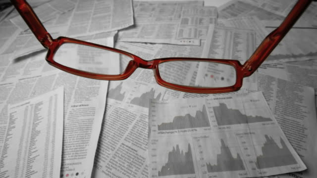 glasses falling over sheets of paper showing graphs and data - graph paper stock videos & royalty-free footage