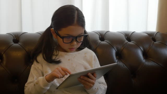 glasses girl using tablet on sofa moving slider right to left - タブレット使用点の映像素材/bロール