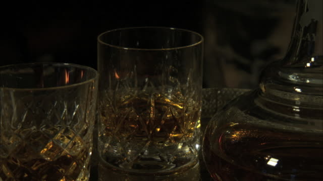 """ms 2 glasses of scotch malt whisky with decanter and fireside lighting. """"islay"""" engraved on the decanter - decanter stock videos & royalty-free footage"""