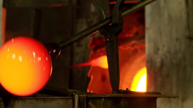cu glassmaker blowing hot glass in front of the furnace - glasbläser stock-videos und b-roll-filmmaterial