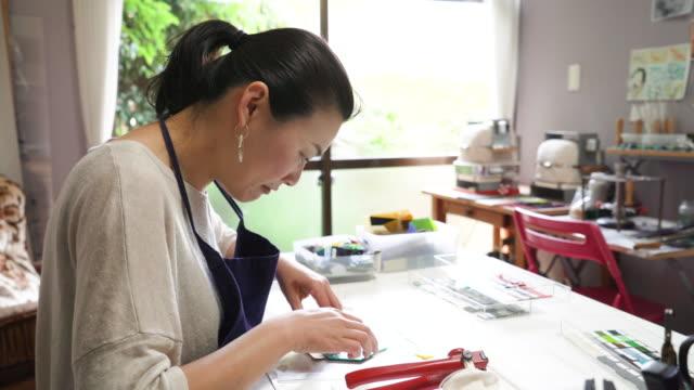 ガラス器製造職人が自宅のアトリエでガラス アクセサリーを作る - 中年点の映像素材/bロール