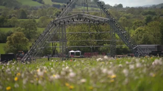 'live at worthy farm' event set up; england: somerset: pilton: worthy farm: ext gvs worthy farm with pyramid stage under construction, cows in... - rock formation stock videos & royalty-free footage