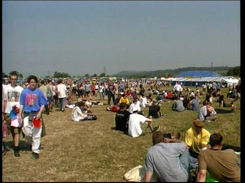 Glastonbury music festival ITN Somerset Glastonbury Stage PAN to sparse audience sitting by it GV People to and fro Order Ref BSP250699016