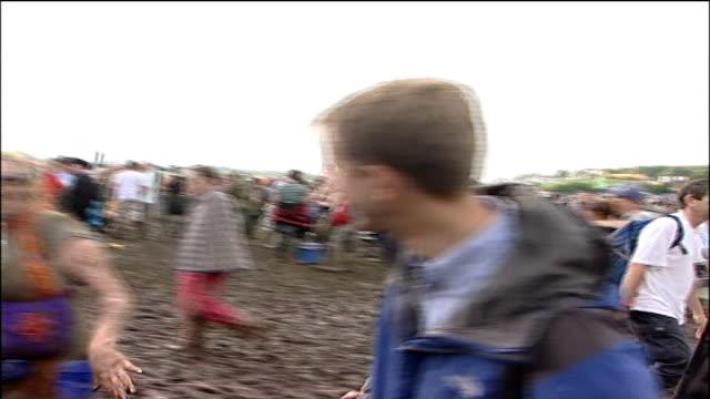 glastonbury music festival; vox pops muddy festival-goer - festival goer stock videos & royalty-free footage