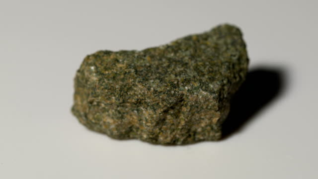 glauconite sandstone mineral sample in rotation with white background