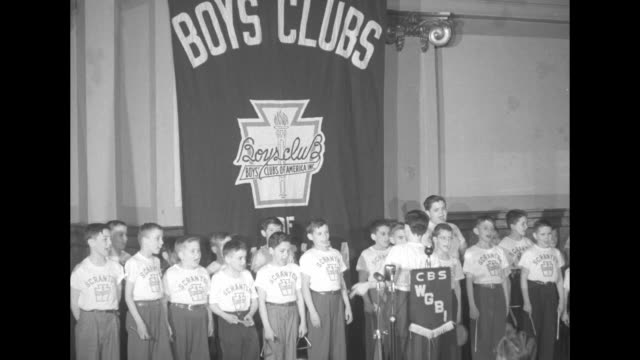 Glee club of boys singing they wear tee shirts with Scranton and Boys' Clubs logo on them behind them hangs a large banner reading Boys' Clubs with...