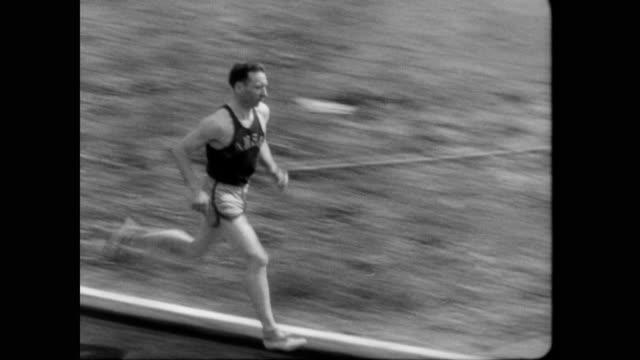 / glen cunningham races glen dawson at kansas relay / crowd cheers as cunningham wins. glen cunningham wins kansas track relay on april 20, 1935 in... - 1935 stock-videos und b-roll-filmmaterial