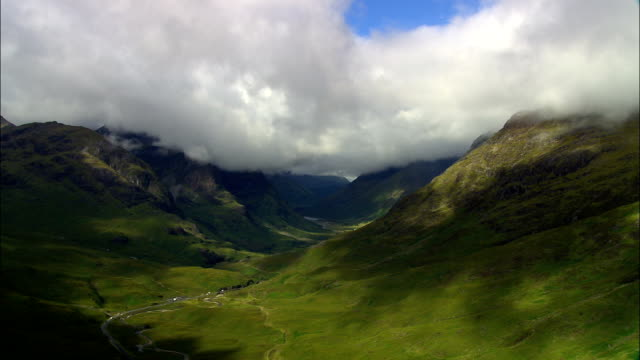 glencoe and mountains with clouds  - aerial view - scotland, highland, united kingdom - scottish highlands stock videos & royalty-free footage