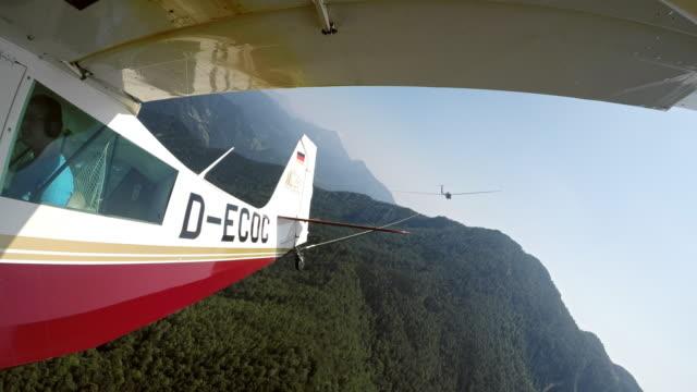 ld-segelflugzeug geschleppt durch ein leichtflugzeug hoch in den sonnigen himmel - segelflugzeug stock-videos und b-roll-filmmaterial