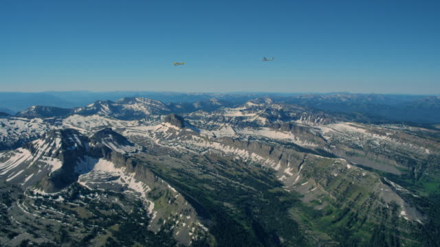 Glider being towed by airplane over the Grand Teton Mountains