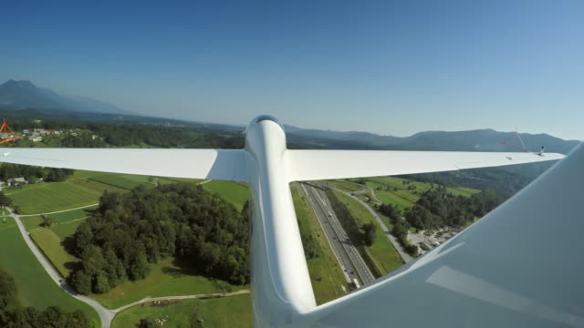 ld glider being towed in the air above the green landscape - glider stock videos & royalty-free footage