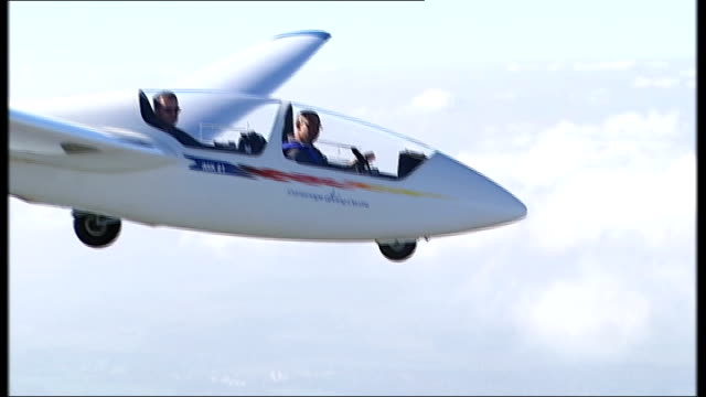vídeos de stock, filmes e b-roll de glider coming into land on airfield instructor making sure reporter fixed up with bailout equipment glider taking off from airfield reporter to... - planador