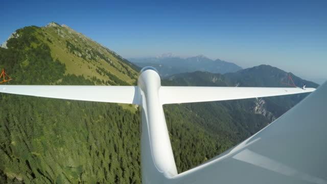 ld segelflygplan gör slingor i soliga himlen ovanför det lummiga gröna landskapet - segelflygplan bildbanksvideor och videomaterial från bakom kulisserna