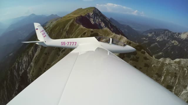 ld glider flying above a green mountain ridge in sunshine - glider stock videos & royalty-free footage