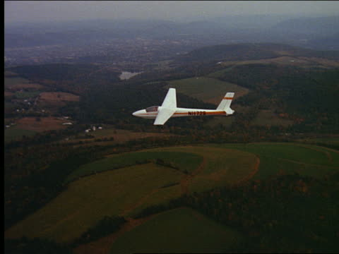 vídeos de stock, filmes e b-roll de aerial glider flying over farmland - planador