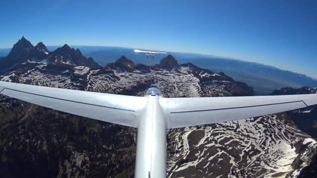 glider flying over the teton mountains viewed from the tail wing - grand teton stock-videos und b-roll-filmmaterial