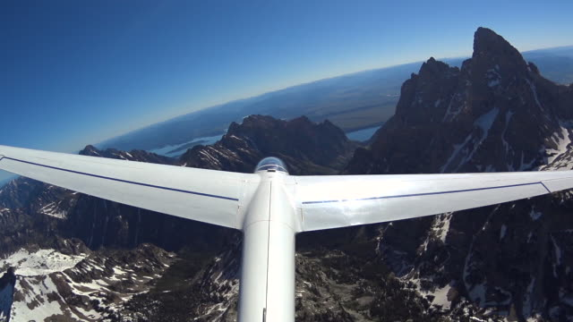 glider flying viwed from tail wing with grand tetons in background - grand teton stock-videos und b-roll-filmmaterial