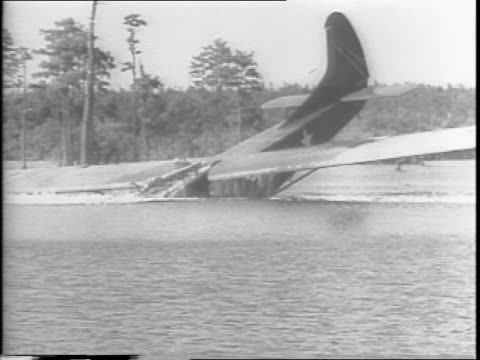 a glider is landed in the water / the nose diving into the surface and then leveling out / the soldiers emerge wading then running with their rifles... - anno 1943 video stock e b–roll