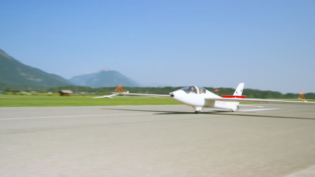 glider landing on the sunny airstrip - glider stock videos & royalty-free footage