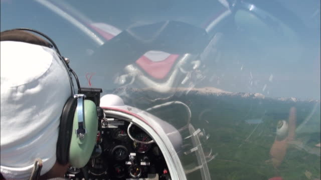 a glider pilot peers through a cockpit window above a forest in hokkaido, japan. - gliding stock videos and b-roll footage