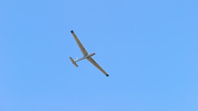 glider plane moving across the blue sky - glider stock videos & royalty-free footage