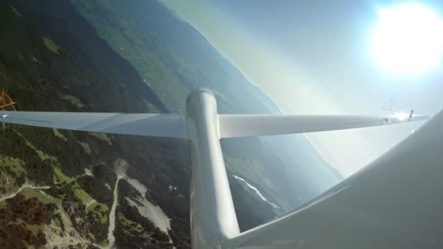 ld glider sailing above a green mountain ridge on a sunny day - glider stock videos & royalty-free footage