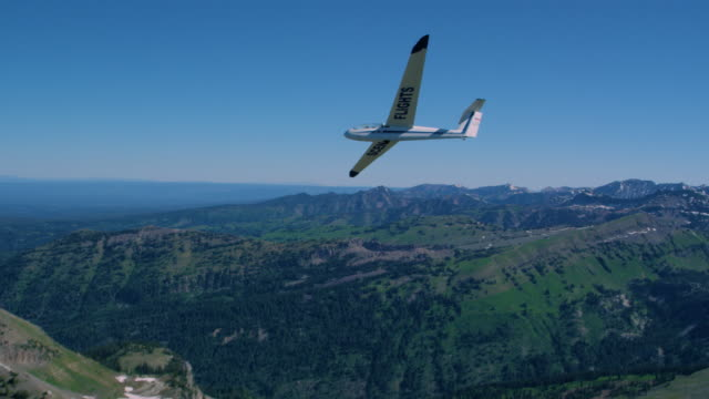 glider turning over the teton mountain range. - gliding stock videos and b-roll footage
