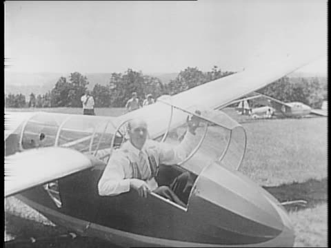 Gliders float through the air at great altitude / a glider lands in a field and General Henry Arnold emerges / Arnold inspects gliders on the ground...