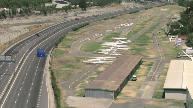 2010 aerial gliders parked next to major highway / santiago de chile, gran santiago, chile - major road stock-videos und b-roll-filmmaterial