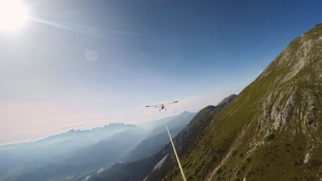 pov gliding along a mountain ridge in a sailplane in sunshine - rope stock videos & royalty-free footage