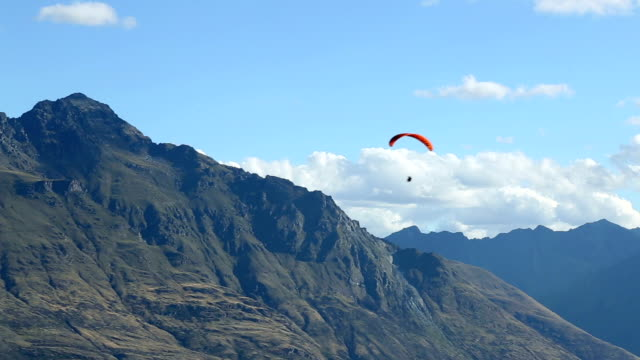 gliding parachute over mountains in blue sky - hang gliding stock videos and b-roll footage