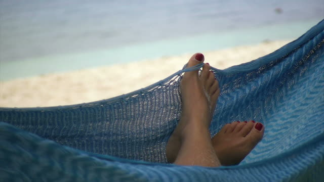 Glimpse of a woman's feet relaxing in a blue hammock on a beach.