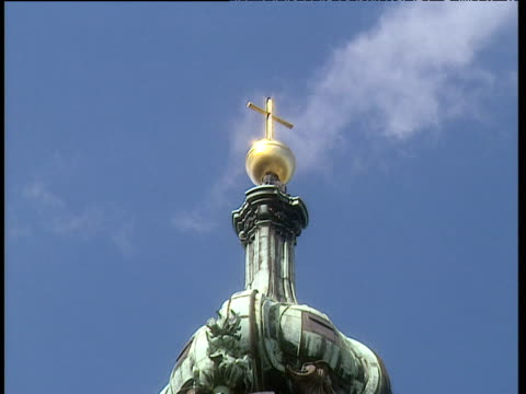 glistening gold cross mounted on green dome of catholic church against blue sky with wisp of cloud floating in background bavaria. - catholicism stock videos & royalty-free footage