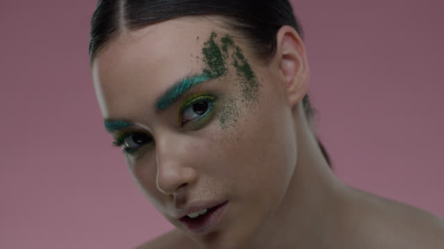 glitter is poured on fashion model's face. - greasepaint stock videos and b-roll footage