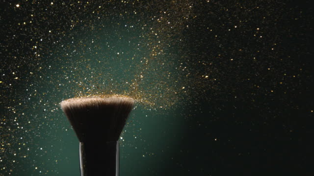 vídeos de stock, filmes e b-roll de glitter on a make-up brush flying away with woman finger flicking shot in slow motion on green aqua menthe color background - purpurina