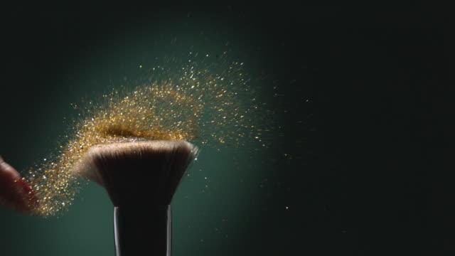 vídeos de stock, filmes e b-roll de glitter on a make-up brush flying away with woman finger flicking shot in slow motion on green aqua menthe color background 4k - purpurina