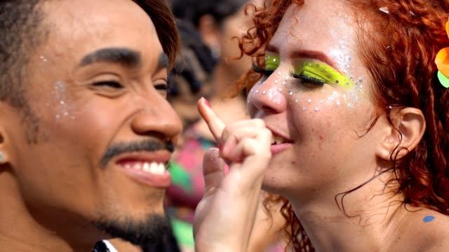 vídeos de stock, filmes e b-roll de glitter pintado de rostos no carnaval - purpurina