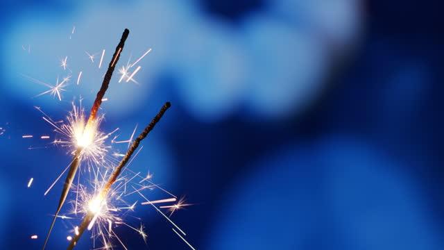 glitzernde brennende wunderkerzen auf dem blauen hintergrund - hell beleuchtet stock-videos und b-roll-filmmaterial