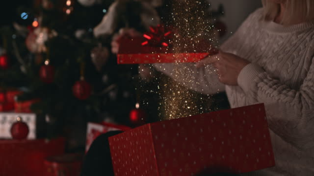 slo mo glittering golden dust blowing out of the christmas present - advent stock videos & royalty-free footage