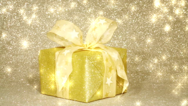 glittering golden gift box with shining stars - tied bow stock videos & royalty-free footage